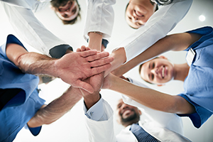care team members standing in a circle putting their hands together in the middle
