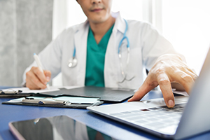 physician entering data on laptop