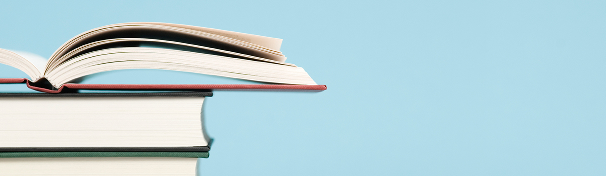 Stock image of a stack of books with the top book flipped open