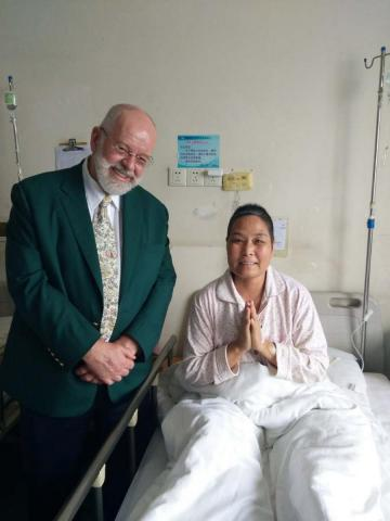Dr. Ferris and a patient in a hospital bed at the International Palliative Care Workshop, Luoyang China